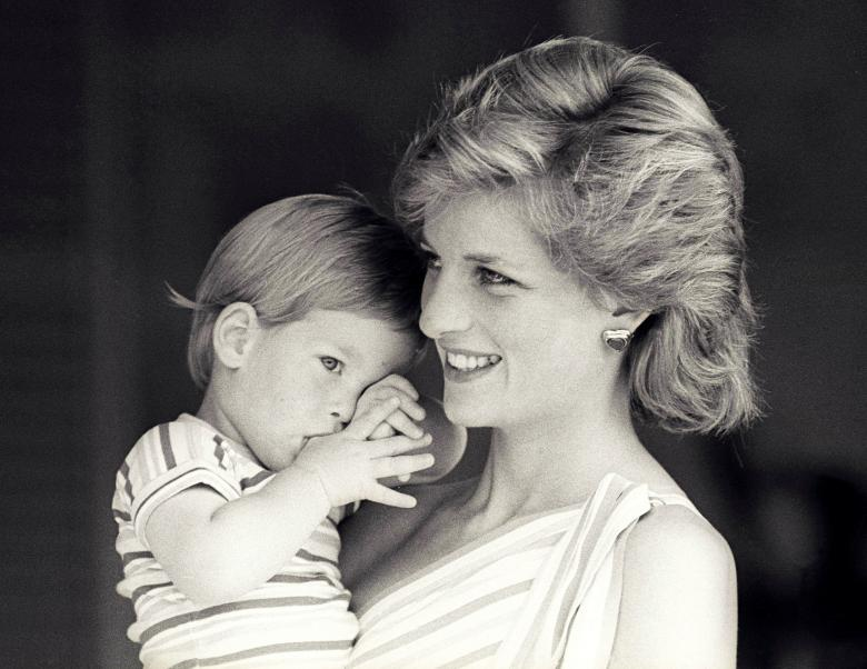 Young Prince Harry tries to hide behind his mother during a morning picture session at Marivent Palace, August 1988.