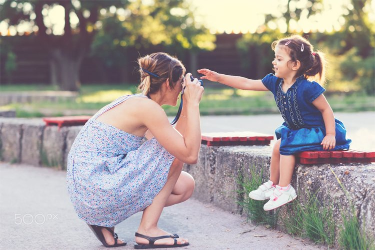 Mother taking photo of her child with old camera